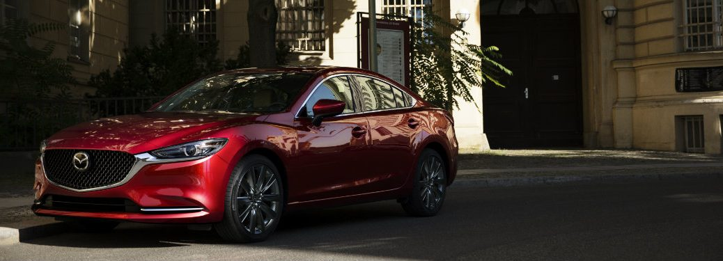 left side view of red mazda6 driving in shadows