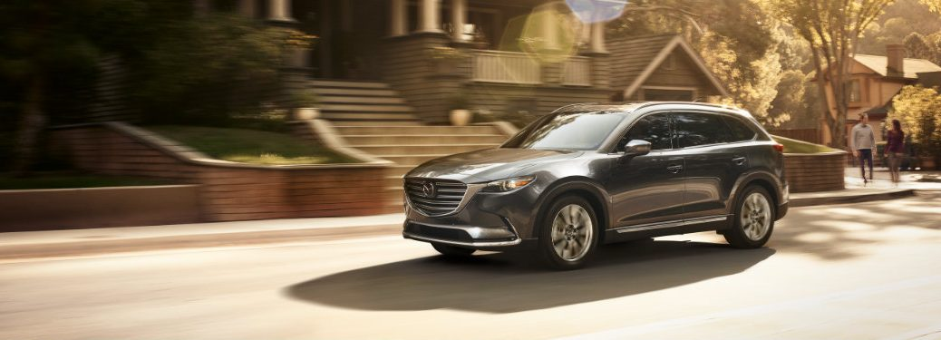 left side view of dark gray mazda cx-9 driving by houses