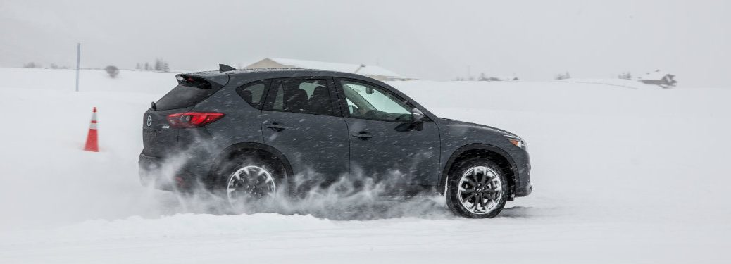 right side view of gray mazda cx-9 driving in snow