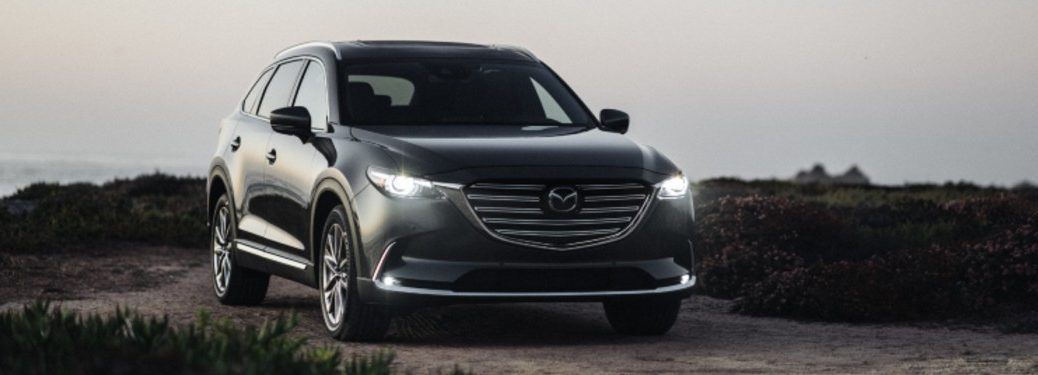 A black 2020 Mazda CX-9 with its lights on at dusk driving down a dirt road.