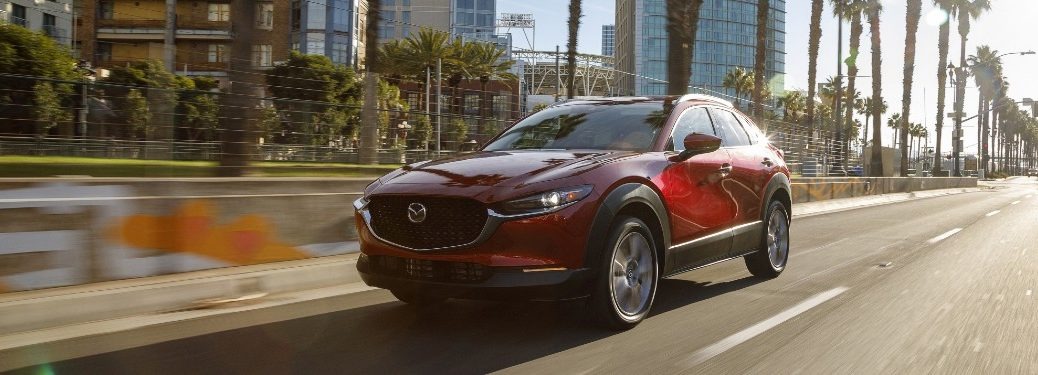 A red 2020 Mazda CX-30 driving quickly down an open city road.