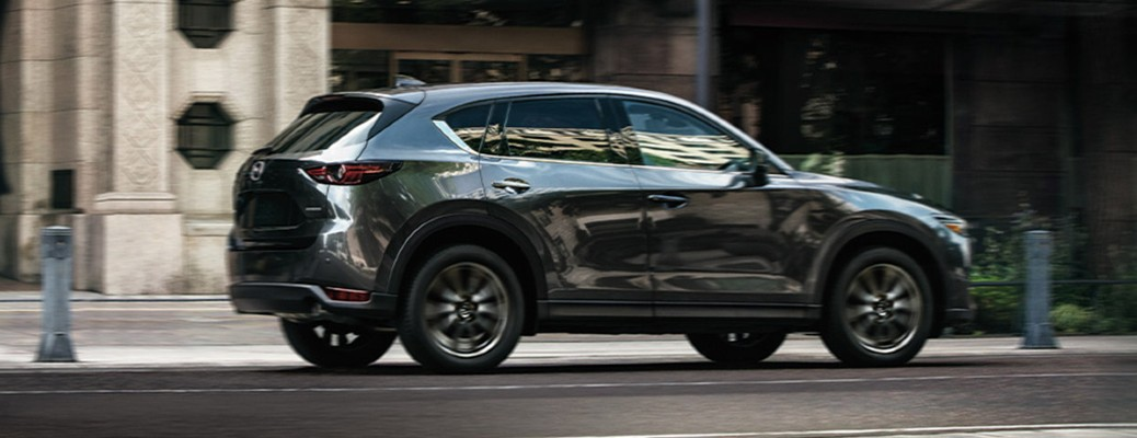 The side view of a gray 2020 Mazda CX-5 driving down a city road.