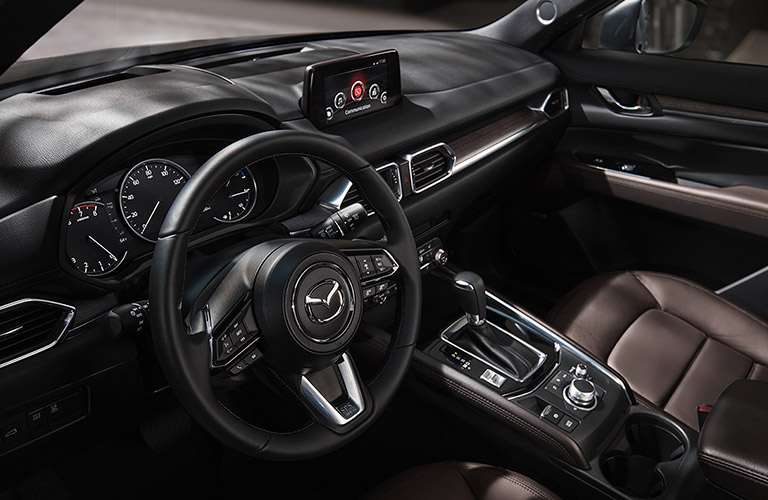 The steering wheel and center console inside of a 2020 Mazda CX-5.