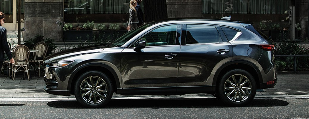 The side image of a gray 2020 Mazda CX-5 parked in a city road.