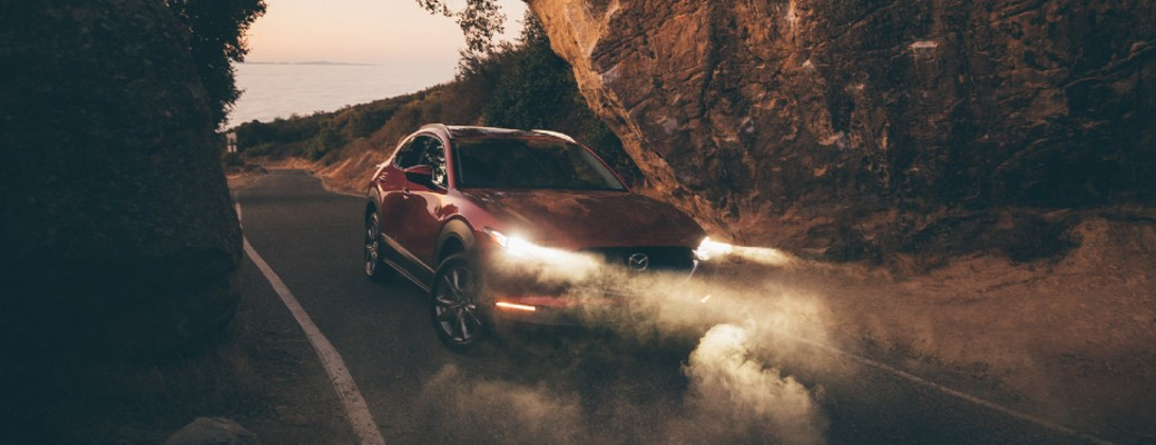 A red 2020 Mazda CX_30 with its lights on surrounded by fog.