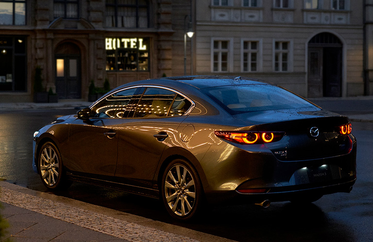 A gray 2020 Mazda3 Sedan parked on a street at night with its lights on.