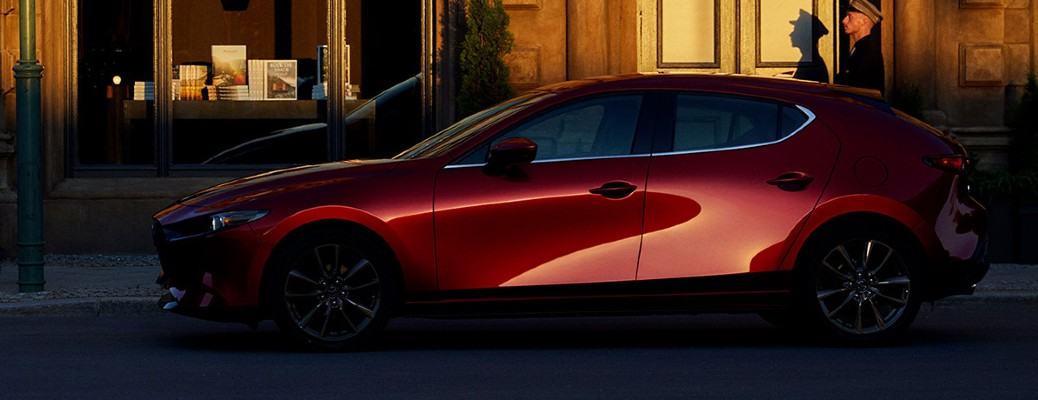 The side view of a red 2020 Mazda3 Hatchback.