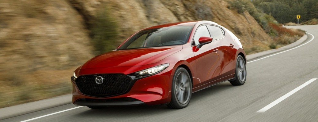 The front and side view of a red 2021 Mazda3 Hatchback driving down a road.