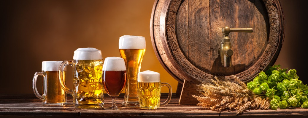 Several beer mugs sitting next to a wooden beer barrel.
