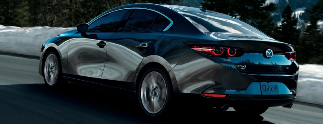 The side and rear view of a gray 2021 Mazda3 Sedan driving down a road.
