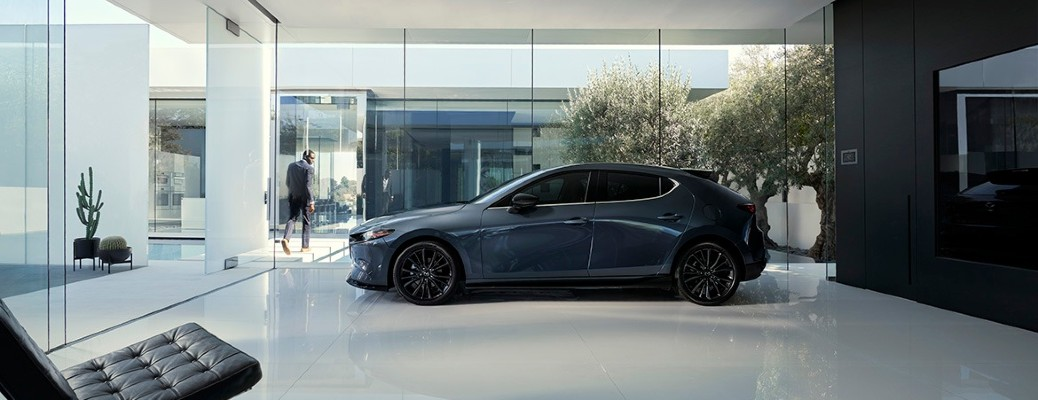 Te side image of a gray 2021 Mazda3 Hatchback Turbo option parked on display inside a building.