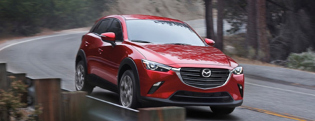 The front and side view of a red 2021 Mazda CX-3 driving down an open road.