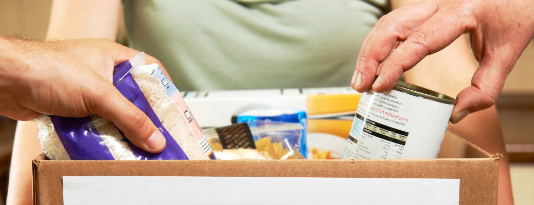 A group of people donating to a box about to be sent to a food bank.