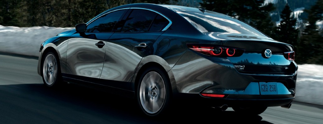 The rear view of a gray 2021 Mazda3 Sedan driving down a road.