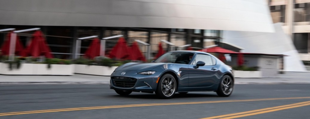 The front and side view of a gray 2021 Mazda MX-5 Miata.