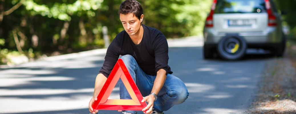 A young man putting out a warning sign behind his vehicle.