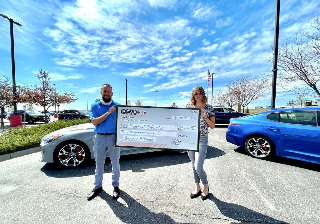 peak kia north dealership donates over 3k to project self-sufficiency. President of Peak Kia North holding  check with Kerrie Luginbill from Old Town Media