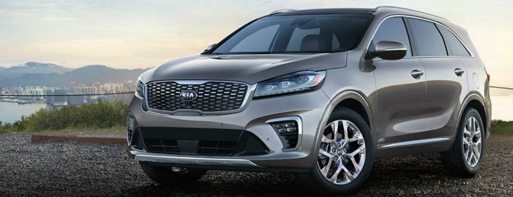 Gray 2019 Kia Sorento parked in front of lake with city skyline in background