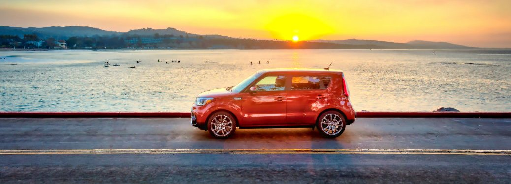orange kia soul driving by water and sunset