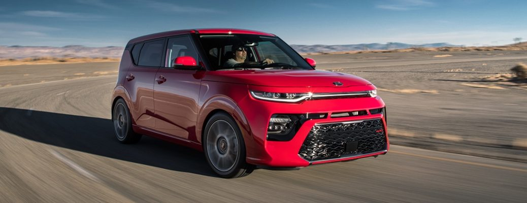 Exterior view of an Inferno Red 2020 Kia Soul driving down a desert highway