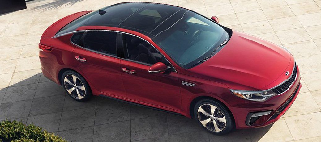 Exterior view of a Passion Red 2019 Kia Optima parked in a driveway