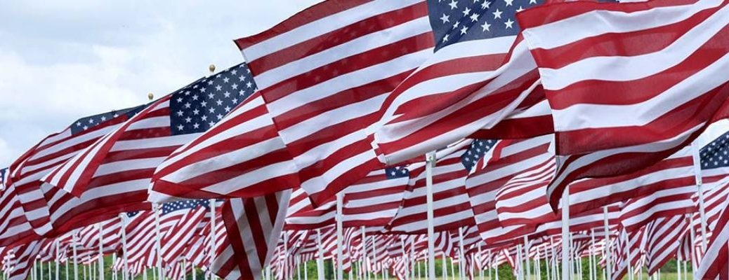 Memorial Day header with many small American Flags blowing in the wind