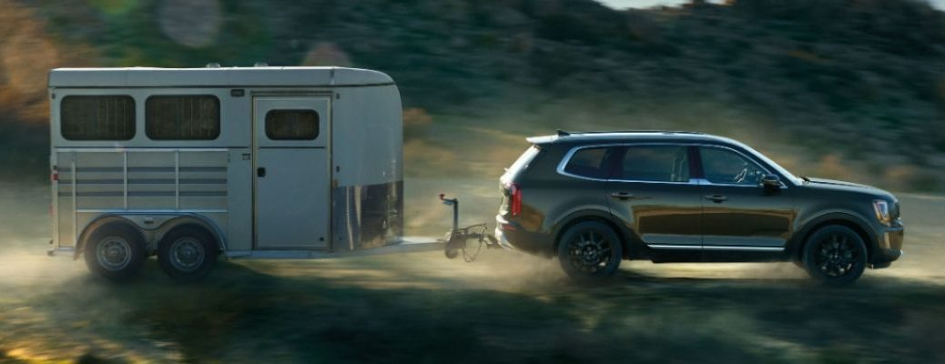 Exterior view of a green 2020 Kia Telluride towing a trailer
