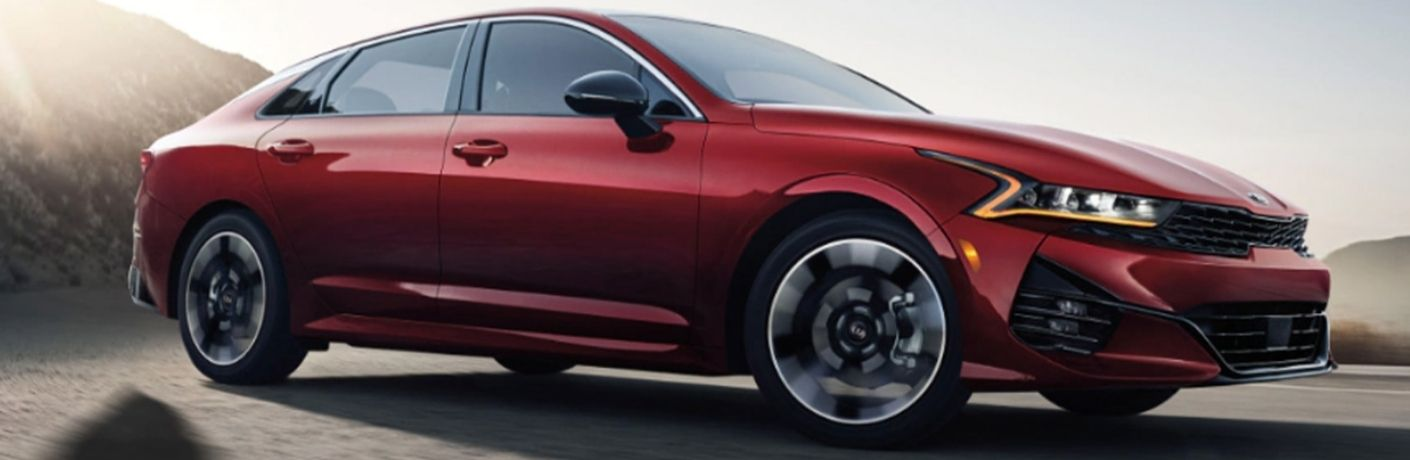 View of the 2022 Kia K5 in red with a mountain background