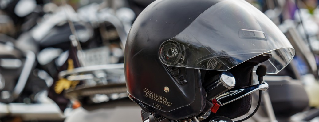 An image of a harley Davidson helmet sitting on top of a motorcycle's handlebars.