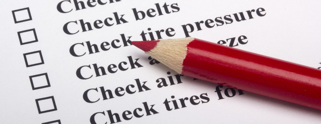 A checklist of items for a vehicle with a red pencil sitting on top of the list.