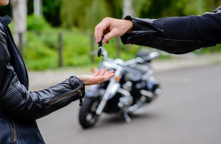 A person handing the keys over to another person to drive a motorcycle.