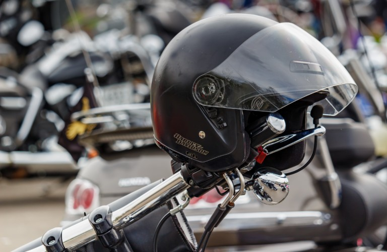 A motorcycle helmet sitting on top of a motorcycle handlebar.