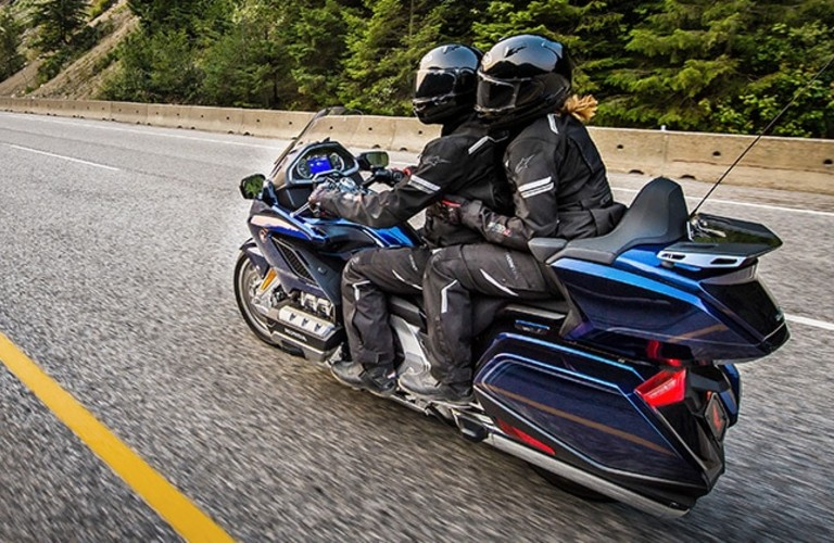 Two people on a 2020 Honda GoldWing model being driven down the road.