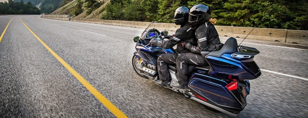 Two riders on a Honda Goldwing motorcycle driving down an open road.