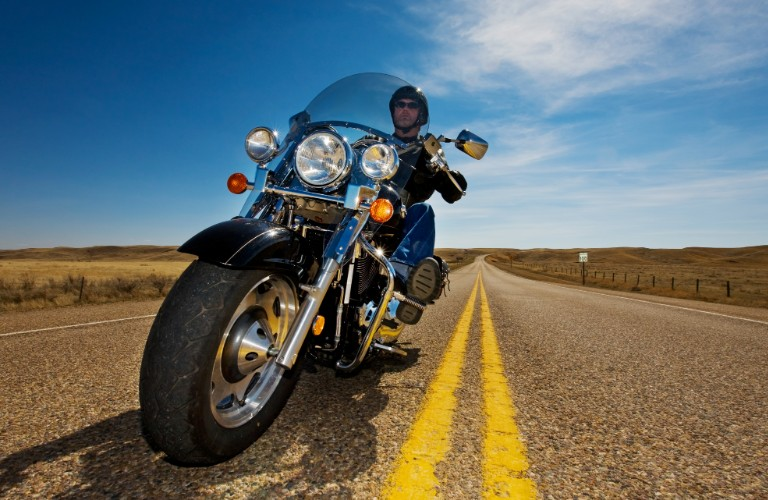 A man driving down an open road in the sunlight wearing a leather jacket.