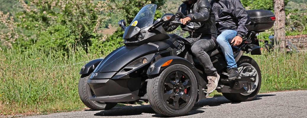 A couple riding on a black CAN-AM Spyder, which is a tricycle.