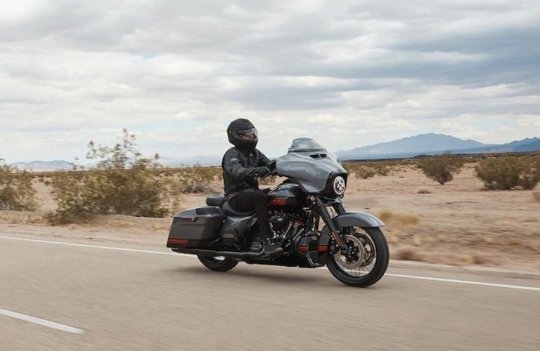 The side view of a black 2020 Harley-Davidson Street Glide driving down an open road.