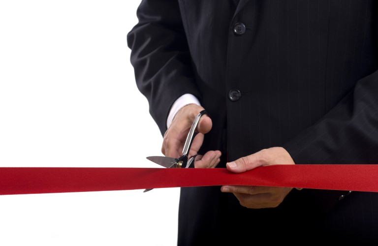 A man cutting a ribbon at a ceremony.