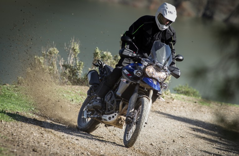 A man driving an off-road motorcycle that is equipped with headlights and side mirrors.