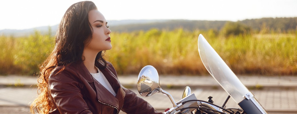 A woman on a motorcycle in the sunlight.