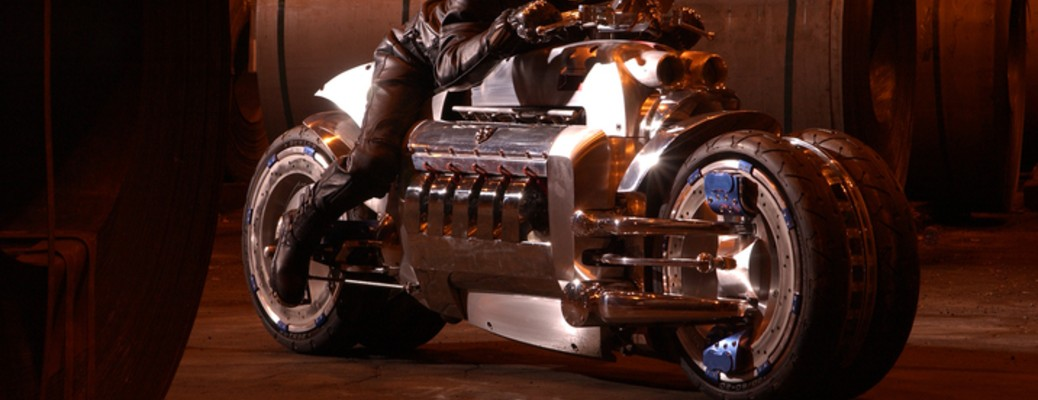 A rider sitting on a silver Dodge Tomahawk concept motorcycle in a side alley at night.