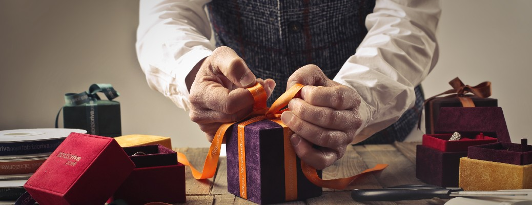 An elderly man tying a bow on a present on a table.