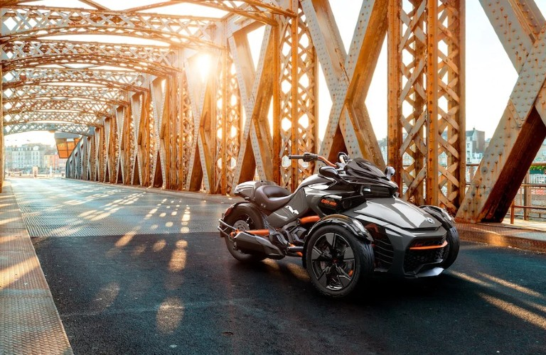 The front view of a 2021 Can-Am Spyder parked on an iron bridge.