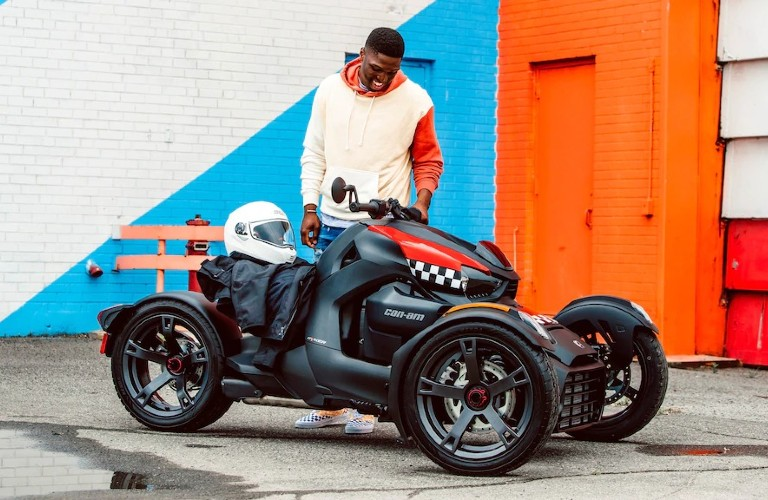A young man getting ready to sit on a black 2021 Can-Am Ryker.