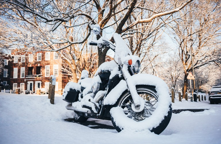 A black motorcycle covered in snow after a snow storm.