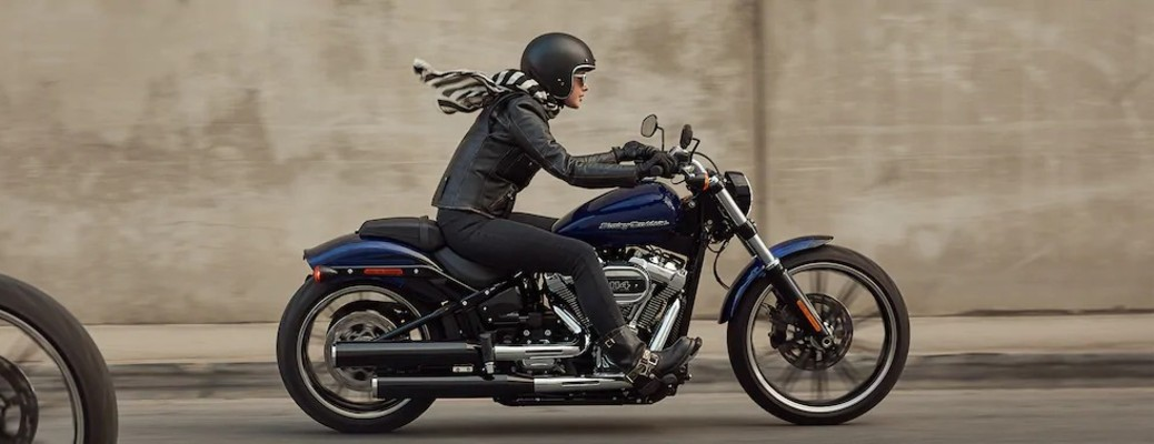 The side view of a woman driving a 2020 Harley-Davidson Breakout 114.