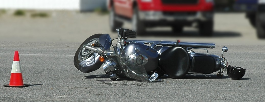 A black motorcycle that's fallen over in the road next to a traffic cone.