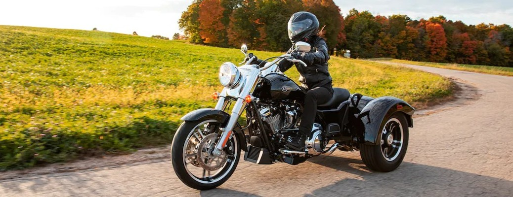 The side view of a driver riding on a 2021 Harley-Davidson® Freewheeler.