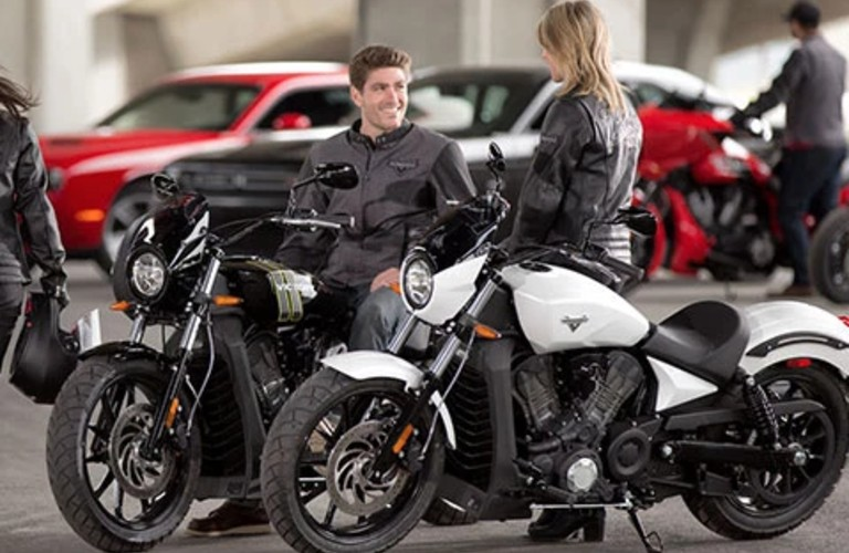 A young couple sitting on a black and white 2017 Victory motorcycles.