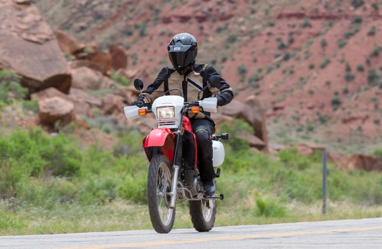 A driver on top of a white and red 2020 Honda XR650L.